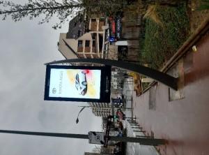 Publicités sur le totem numérique Conseil départemental et derrière  la vitrine d'un Monoprix au même moment.